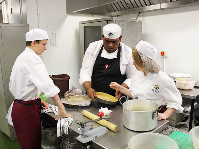 Level 2 Cookery student Akmol Hussain helps Courtney Jordan prepare dessert