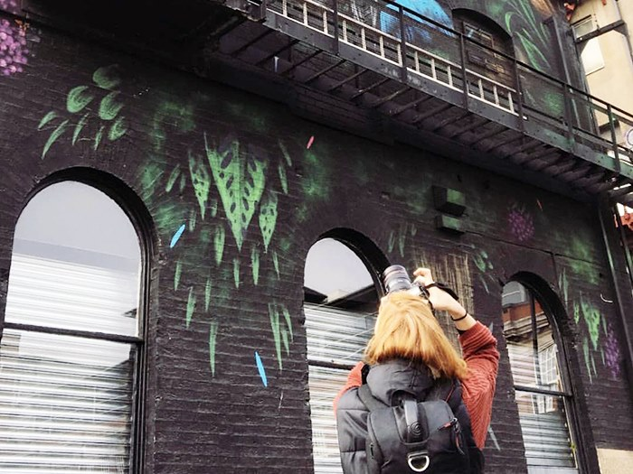 Student photographing a mural