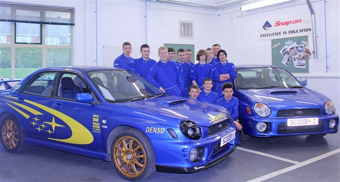 Students in the Motorsport workshop, standing with not one, but two Subaru Imprezas they are currently working on.